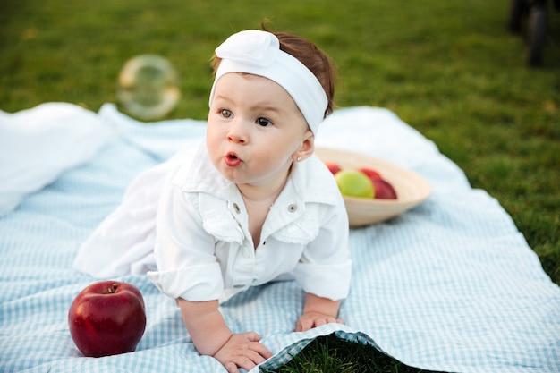 Urocza mała dziewczynka bawi się na pikniku w parku