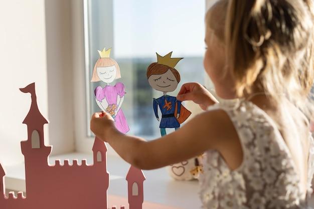 Urocza mała dziewczynka bawi się swoimi lalkami w domu