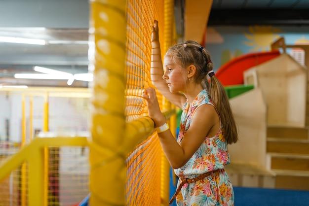 Urocza mała dziewczynka bawi się w labiryncie dla dzieci, plac zabaw w centrum rozrywki.