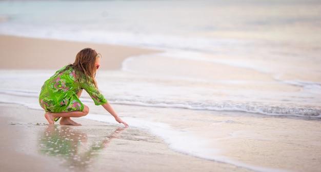 Urocza mała dziewczynka bawić się na tropikalnej plaży podczas wakacje