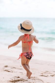 Urocza mała dziewczynka bawić się na tropikalnej plaży podczas wakacji