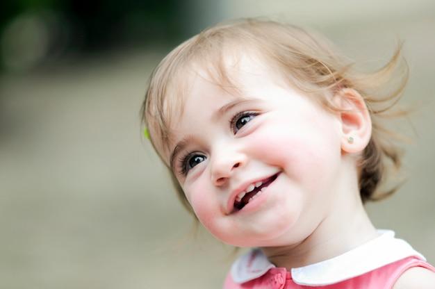 Urocza mała dziewczynka bawić się w miastowym parku