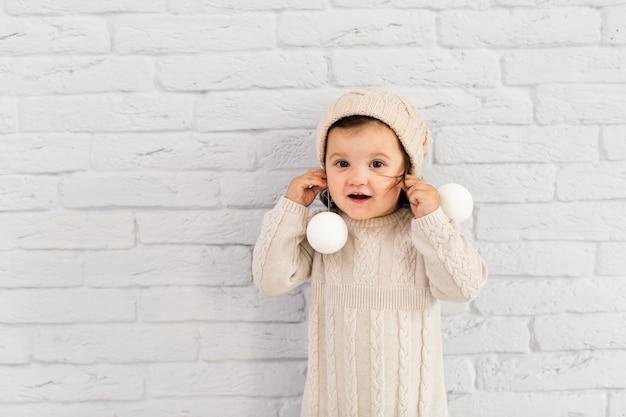 Urocza mała dziewczynka bawić się z boże narodzenie kulami ziemskimi