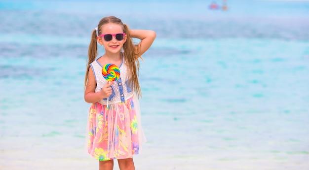 Urocza mała dziewczynka bawić się z lollipop na plaży