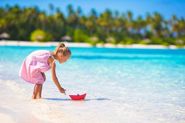 Urocza mała dziewczynka bawić się z origami łodzią w turkusowym morzu