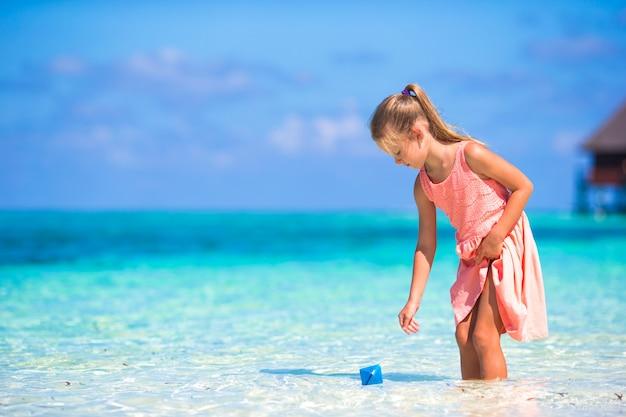 Urocza mała dziewczynka bawić się z papierową łodzią w turkusowym morzu