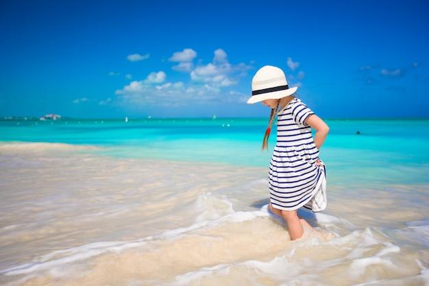 Urocza mała dziewczynka biega w płytkiej wodzie przy egzotyczną plażą