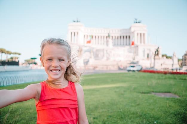 Urocza mała dziewczynka bierze selfie przed altare della patria, vittoriano, rzym, włochy.