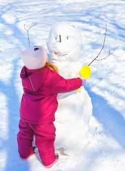 Urocza mała dziewczynka buduje bałwanu w zima parku. słodkie dziecko bawiące się w śniegu.