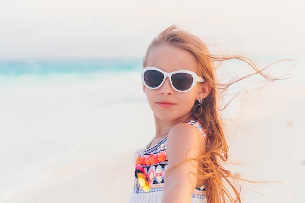 Urocza mała dziewczynka chodzi wzdłuż białej piasek karaiby plaży
