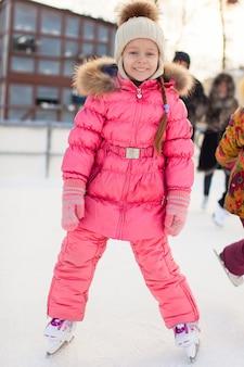 Urocza mała dziewczynka cieszy się jeździć na łyżwach przy lodowiskiem