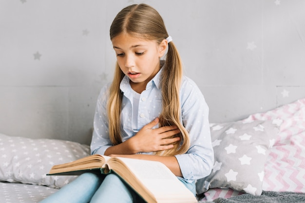 Urocza mała dziewczynka czyta książkę
