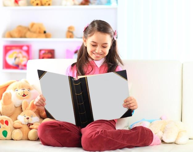 Urocza mała dziewczynka czytanie książki z zabawką na białej kanapie