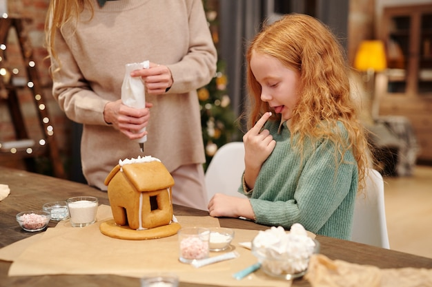 Urocza mała dziewczynka degustująca bitą śmietanę z dachu domowego domku z piernika, podczas gdy jej matka dekorowała go przed świąteczną kolacją
