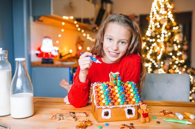 Urocza mała dziewczynka dekorująca dom z piernika glazurą