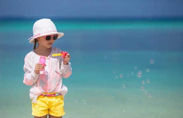 Urocza mała dziewczynka dmucha mydlanych bąble na plaży