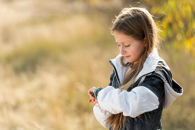 Urocza mała dziewczynka dostosowuje zegarek