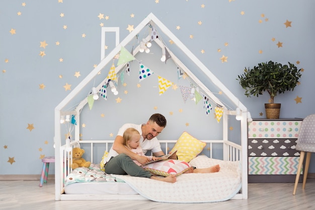 Urocza mała dziewczynka i jej młody tata czytają książkę, siedząc w ozdobnym domowym łóżku w sypialni. wnętrze sypialni dla dzieci
