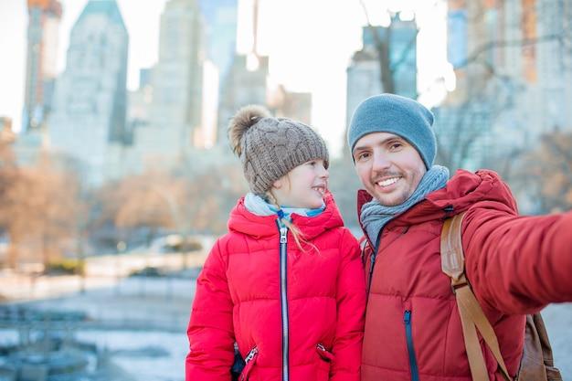 Urocza mała dziewczynka i tata bawią się w central parku w nowym jorku