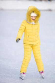 Urocza mała dziewczynka iść łyżwa w zima śnieżnym dniu outdoors