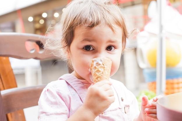 Urocza mała dziewczynka je lody w kawiarni na świeżym powietrzu