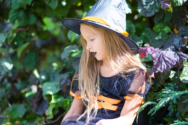 Urocza mała dziewczynka jest ubranym czarownica kostium z miotłą na halloween outdoors. cukierek albo psikus