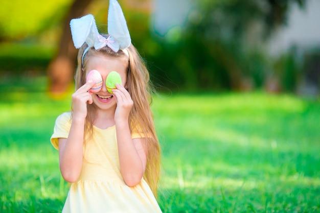 Urocza mała dziewczynka jest ubranym królików ucho z wielkanocnymi jajkami na wiosna dniu
