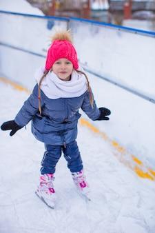 Urocza mała dziewczynka jeździć na łyżwach na lodowisku