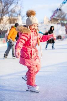 Urocza mała dziewczynka lubi jeździć na łyżwach na lodowisku