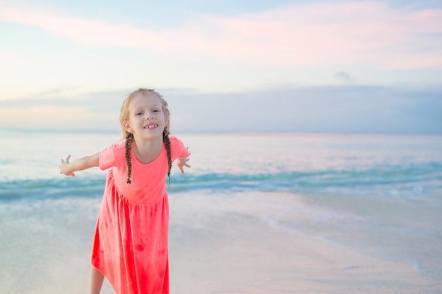 Urocza mała dziewczynka ma dużo zabawy wieczorem na plaży. szczęśliwy dzieciak patrzeje kamery tła pięknego niebo i morze