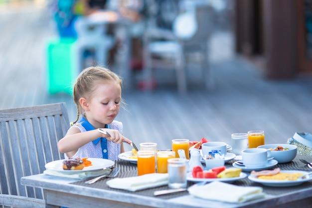Urocza mała dziewczynka ma śniadanie przy plenerową kawiarnią