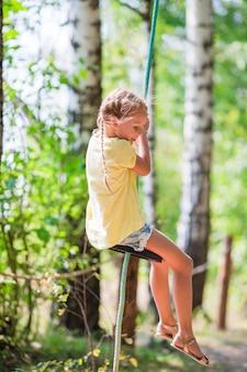 Urocza mała dziewczynka ma zabawę na huśtawce outdoors