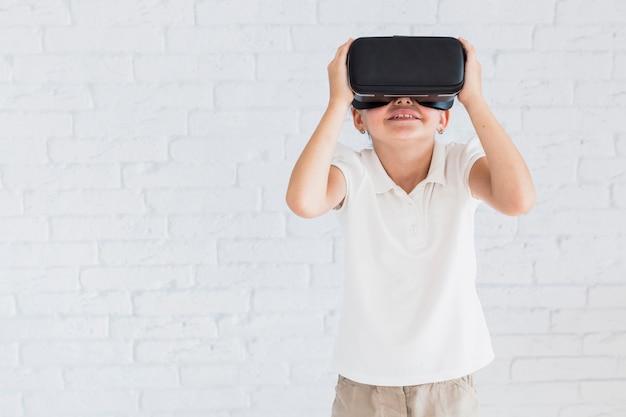 Urocza mała dziewczynka ma zabawę z rzeczywistość wirtualna szkłami