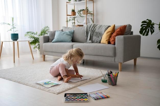 Urocza mała dziewczynka maluje na papierze w domu