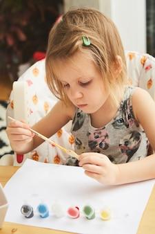 Urocza mała dziewczynka maluje w pokoju. pomysł na samodzielne zajęcia w domu dla dzieci