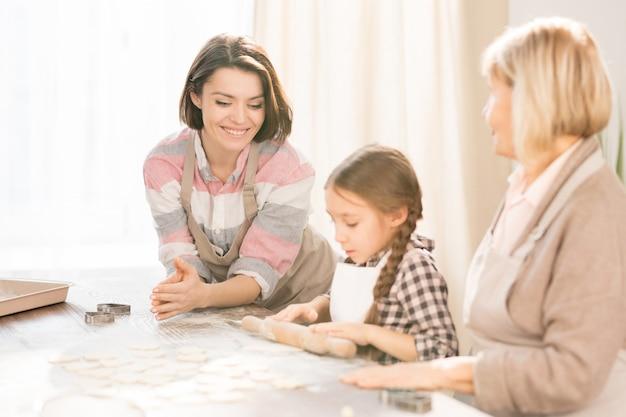 Urocza mała dziewczynka między mamą a babcią za pomocą wałka do ciasta na płasko przed zrobieniem ciasteczek
