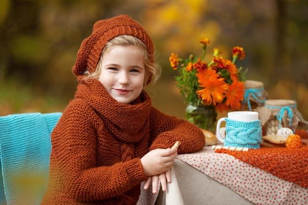 Urocza mała dziewczynka na pikniku w jesiennym parku. śliczna mała dziewczynka o przyjęcie herbaciane w ogrodzie jesienią.