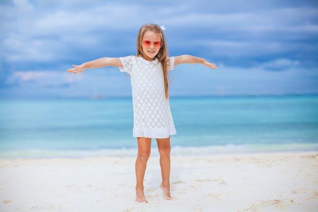 Urocza mała dziewczynka na plaży na wakacjach