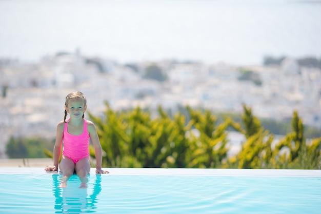 Urocza mała dziewczynka na skraju odkrytego basenu z pięknym widokiem