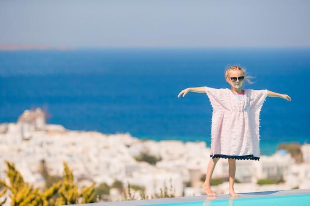 Urocza mała dziewczynka na skraju odkrytego basenu