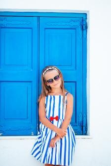 Urocza mała dziewczynka na starej ulicy typowej greckiej tradycyjnej wioski na mykonos