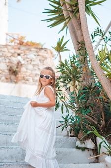 Urocza mała dziewczynka na starej ulicy typowej greckiej tradycyjnej wioski