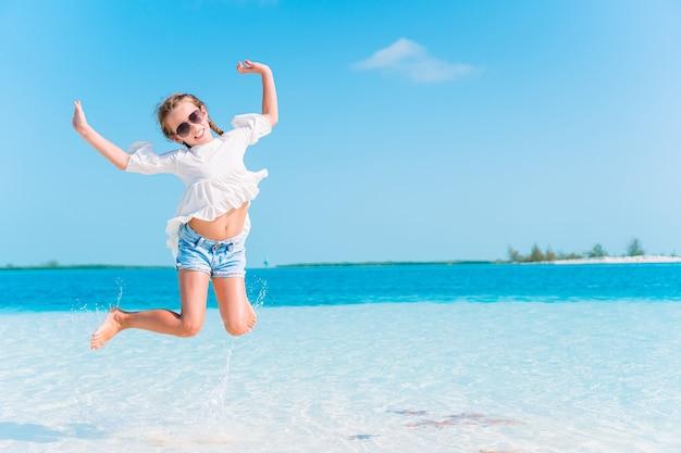 Urocza mała dziewczynka na tropikalnej plaży na wakacjach rozpryskiwania się w płytkiej wodzie