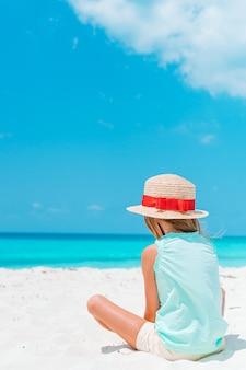Urocza mała dziewczynka na tropikalnej plaży na wakacjach