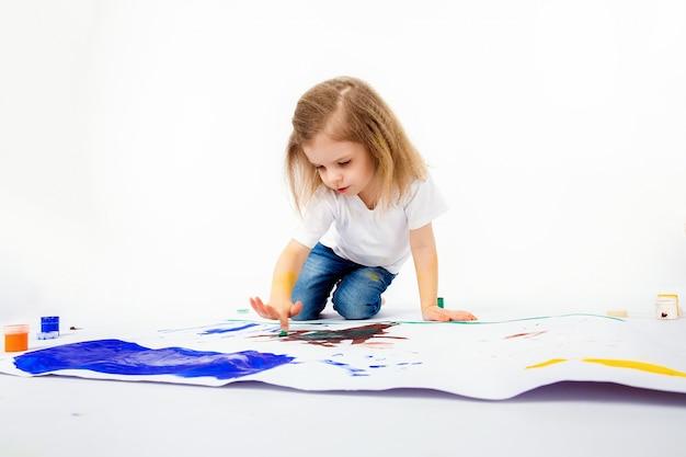Urocza mała dziewczynka, nowoczesna fryzura, biała koszula, niebieskie dżinsy rysuje farbami swoje ręce. izolować.