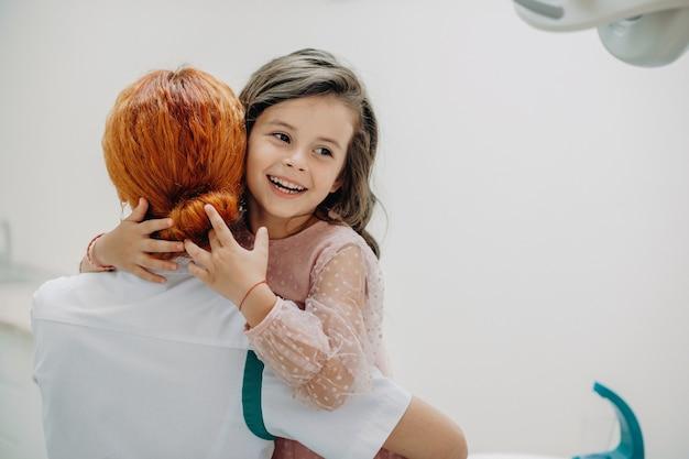 Urocza mała dziewczynka obejmując swojego lekarza po operacji zębów.
