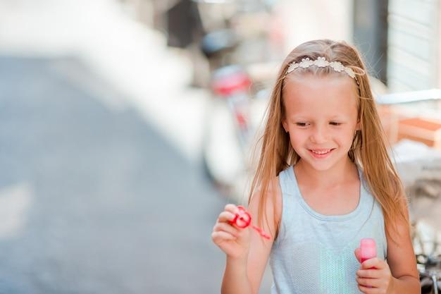 Urocza mała dziewczynka outdoors dmucha mydlanych bąble w europejskim mieście. portret caucasian dzieciak cieszy się wakacje w włochy