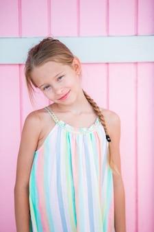 Urocza mała dziewczynka outdoors przeciw kolorowemu domowi