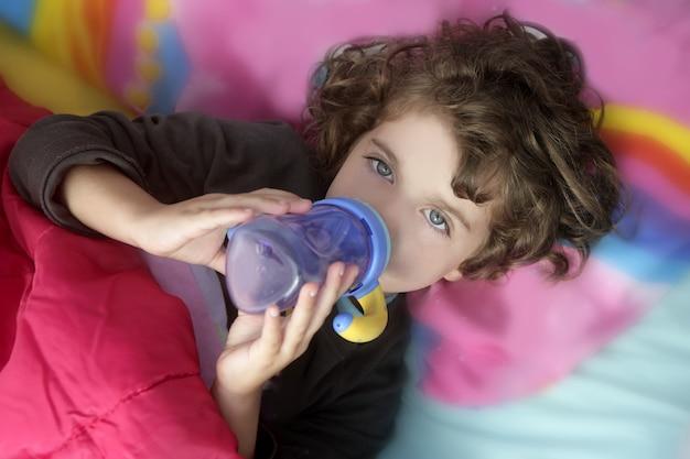 Urocza mała dziewczynka pije butelkę