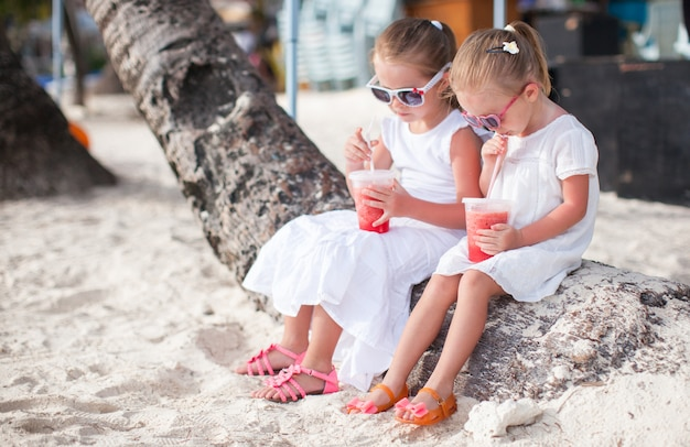 Urocza mała dziewczynka pije świeżego arbuza na plaży